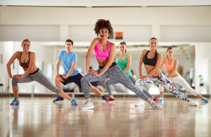 Warming up exercises with female instructor in course at gym