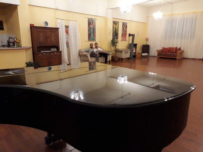 Klavier und Sitzgruppe. Kronleuchter im Reflex